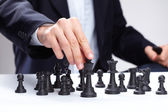 Business man moving chess figure — Stock Photo