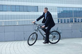 Active businessman riding a bicycle — Stock Photo