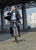 Businessman riding a bicycl — Stock Photo