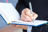 Female hand writing in notebook — Stock Photo