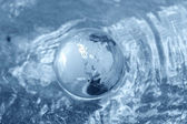 Glass globe on water — Stock Photo