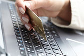 Woman holding credit card on laptop — Stock fotografie