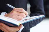 Mujer mano escribir en cuaderno — Foto de Stock
