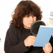 Boy reading a book with lens — Stock Photo #2184420