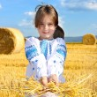 Stock Photo: Small rural girl on harvest field with straw bales