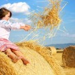 Small rural girl on harvest field with straw bales — Stock Photo