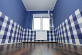 Empty room with a blue wall and blue-white wallpaper — Stock Photo