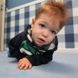 A curious baby boy lying on a floor in room — Stock Photo