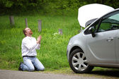 Funny driver praying a broken car by the road   — Stock Photo