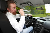 Drunk man in car with a bottle alcohol — Stock Photo