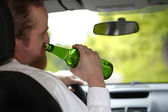 Drunk man in car with a bottle beer — Stock Photo