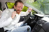 Driver smiling sitting in car and showing new car keys and drive — Stock Photo