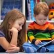 Girl with her little brother fun using a digital tablet computer — Stock Photo #45679283