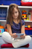 Happy pre-teen girl using a digital tablet computer — Stock Photo