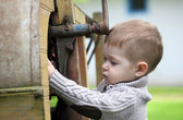 2 years old curious Baby boy managing with old agricultural Mach — Stock Photo