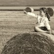 Small rural girl on the straw after harvest field with straw bal — Stock Photo #46239141