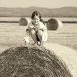 Small rural girl on the straw after harvest field with straw bal — Stock Photo #46239229