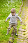 Trendy 2 years old baby boy playing in park — Zdjęcie stockowe