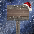 Wooden sign with Santa hat on snowy background — Stock Photo #14020291