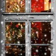 Christmas lights seen through a wooden cabin window — Stock Photo #32755979