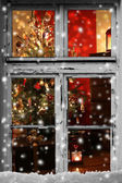 Christmas lights seen through a wooden cabin window — Stock Photo