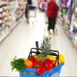 Shopping basket with groceries on shop of background — Stock Photo