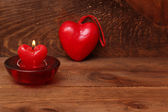Burning candle heart on vintage wooden background — Stok fotoğraf