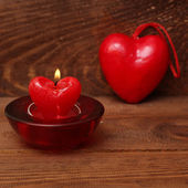 Burning candle heart on vintage wooden background — Stock Photo