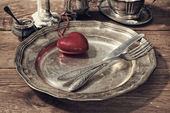 Table setting for Valentine's Day. plate, fork, knife and red hear — Stock Photo