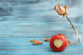 Beautiful rose and apple on romantic blue background — Stock Photo