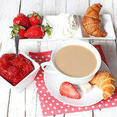Breakfast with croissants, strawberry  and cup of coffe on white — Стоковое фото