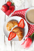 Breakfast with croissants, strawberry  and cup of coffe on white — Stock Photo
