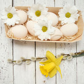 Easter eggs with flowers on wooden background — Stock Photo