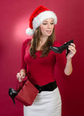 Beautiful woman with Santa Hat holding shoes — Stock Photo