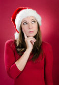 Beautiful young woman with santa hat thinking — Stok fotoğraf