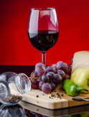 Glass of red wine with grape and vegetables — Stok fotoğraf