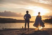 Newly married couple on the river with sunset — Stock Photo