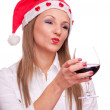 Girl with Santa hat drinking wine and send kiss — Stock Photo