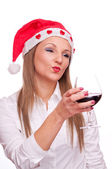Girl with Santa hat drinking wine and send kiss — Stockfoto