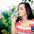 Young woman blowing bubbles — Stock Photo