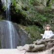 Stock Photo: Little girl meditate by waterfall
