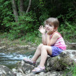 Little girl sitting next to a stream — Stock Photo