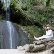 Little girl sitting next to a waterfall — Stock Photo