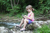 Little girl sitting next to a stream and play with tablet — Stock Photo