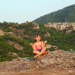 Stock Photo: Little girl sitting on mountain top and meditate