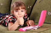 Little girl with thumb up and laptop — Stock Photo