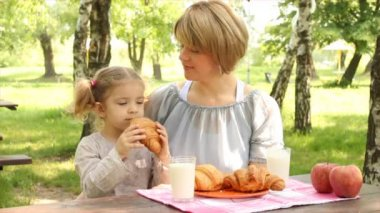 Mother and daughter family breakfast in nature