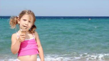 Klein meisje eten ijs op strand — Stockvideo
