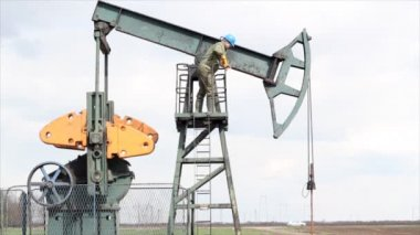 Oil worker standing at the pump jack — Stock Video