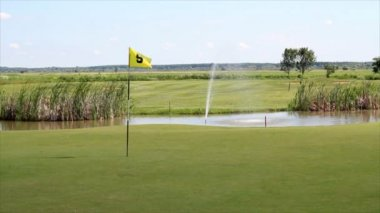 Golf field with yellow flag and pond — Stock Video